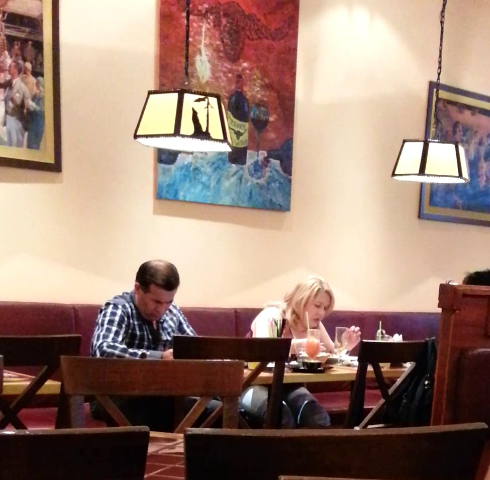 Cantareata mananca de zor, in timp ce sotul ei priveste catre telefonul mobil