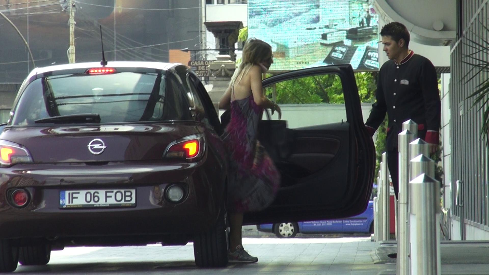 Fara sa se uite la valet, actrita coboara vorbind la telefonul mobil