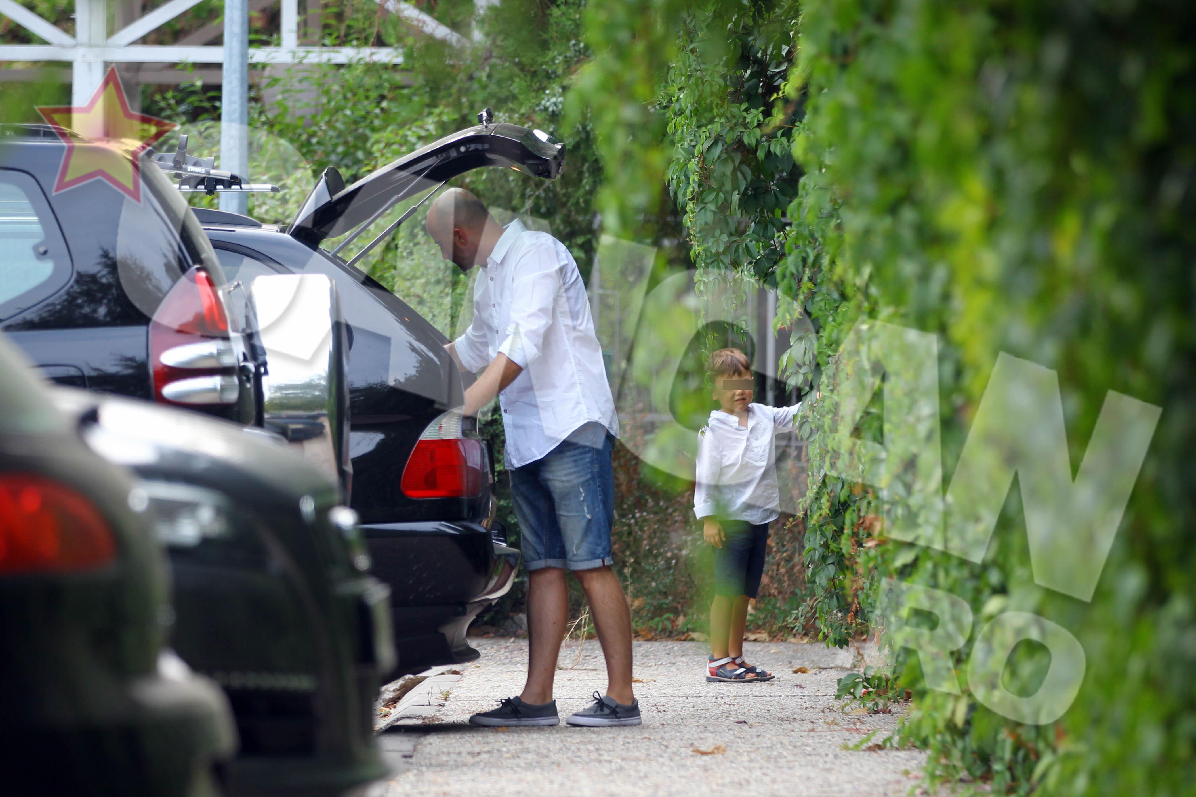 Artistul scoate ceva din portbagajul masinii insa arunca cate o privire si la copii