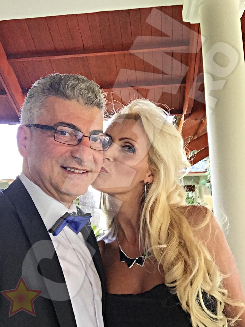 Afaceristul face o fotografie in timp ce ea il saruta pe obraz.