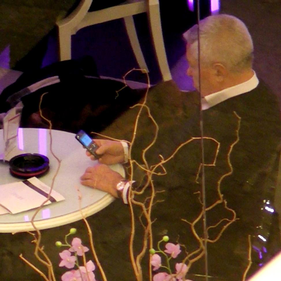 In momentul in care se aseaza la masa, Serban Mihailescu, zis Micky Spaga, cauta un numar in agenta telefonului