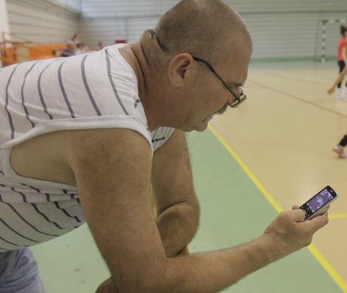 Petre Cozma butoneaza telefonul care i-a apartinut fiului lui si la care nu a renuntat niciun moment