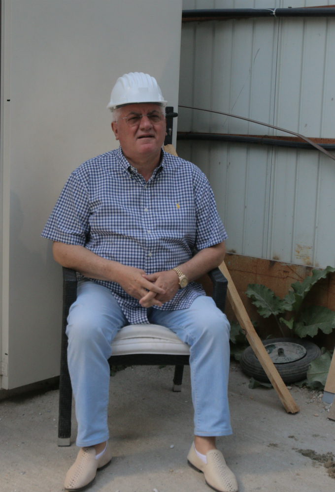 De pe scaun, brigadierul Mitica da ordine pentru muncitorii adusi din satul sau natal, Balcesti