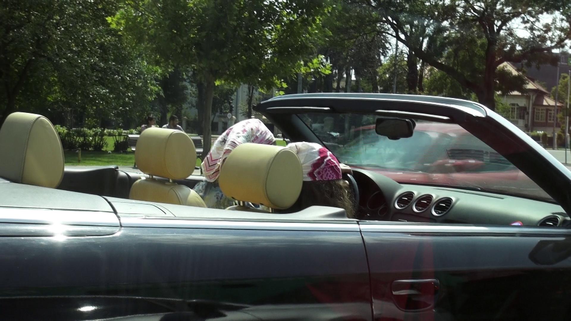 In momentul in care s-a urcat in masina, fiica cea mica i-a urmat exemplul si si-a acoperit capul