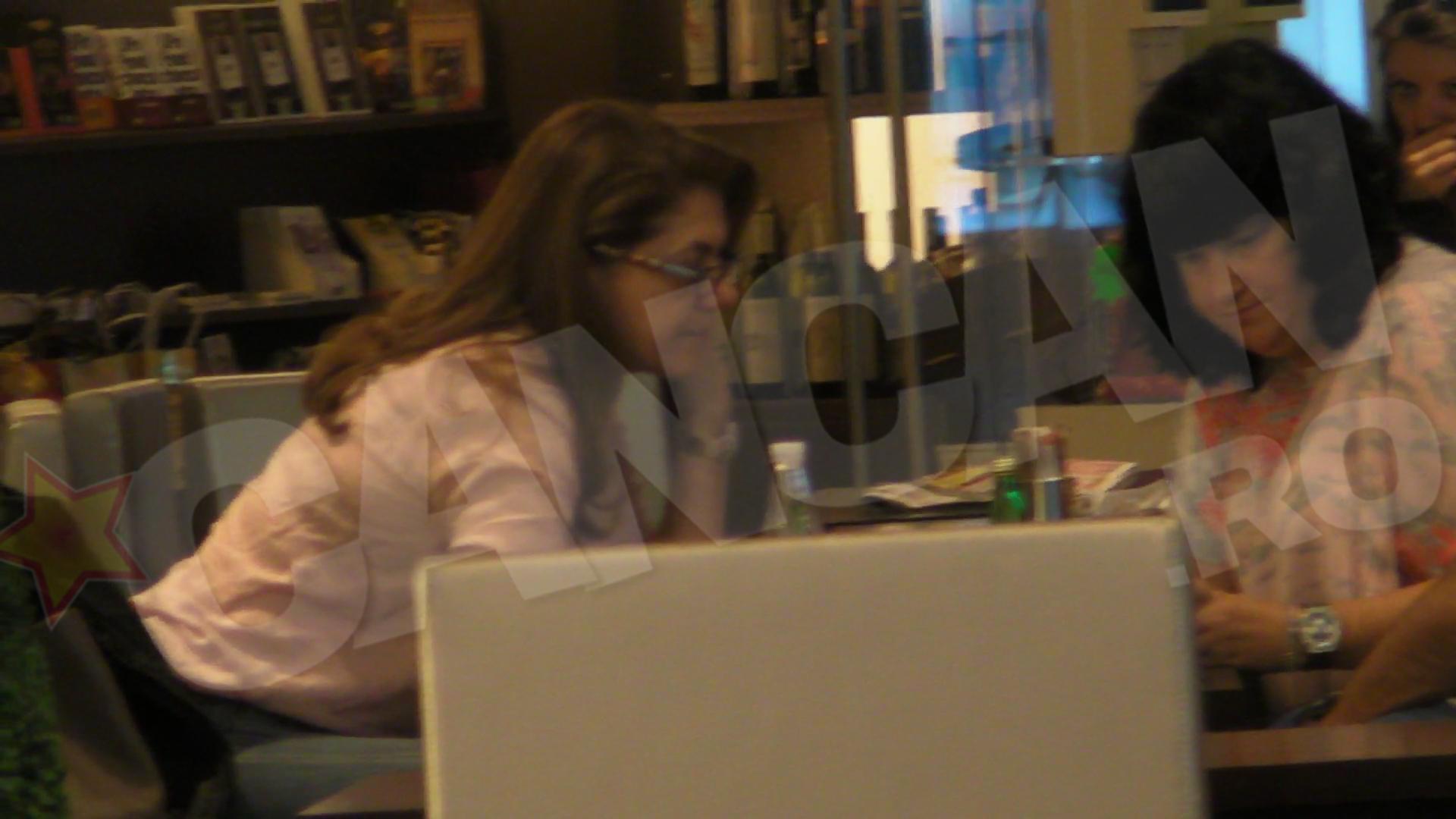 Cealalta femeie de la masa ii arata si ea ceva pe telefonul ei