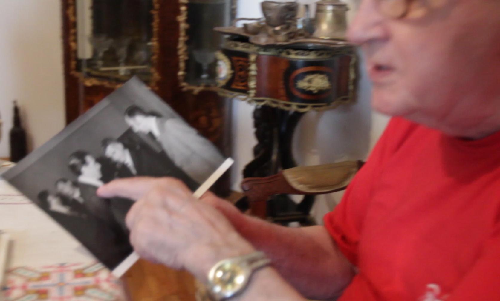 Vasile Anghel se uita pe una dintre fotografiile in care apare alaturi de Nicolae Ceusescu