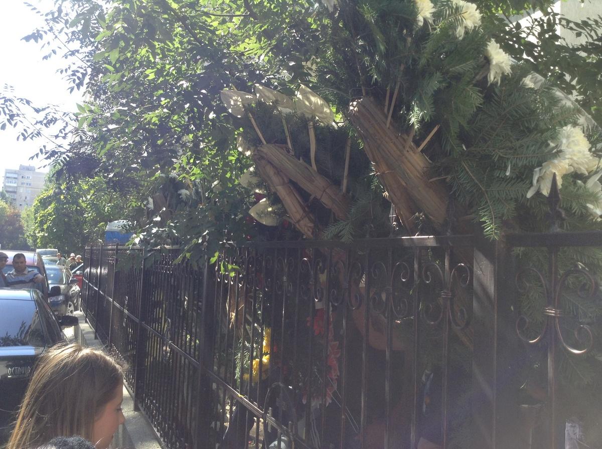 Apropiatii soferului sinucigas au umplut gardul bisericii de coroane pentru ca presa sa nu vada ce se intampla in interior
