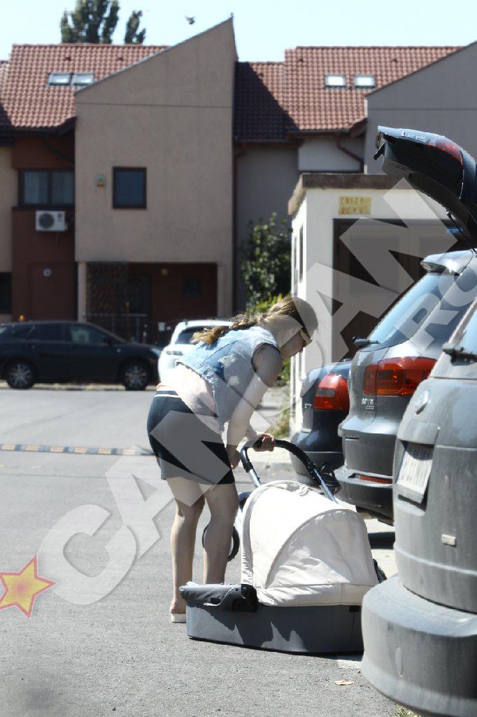 Oana aseaza cu grija caruciorul fetitei in masina