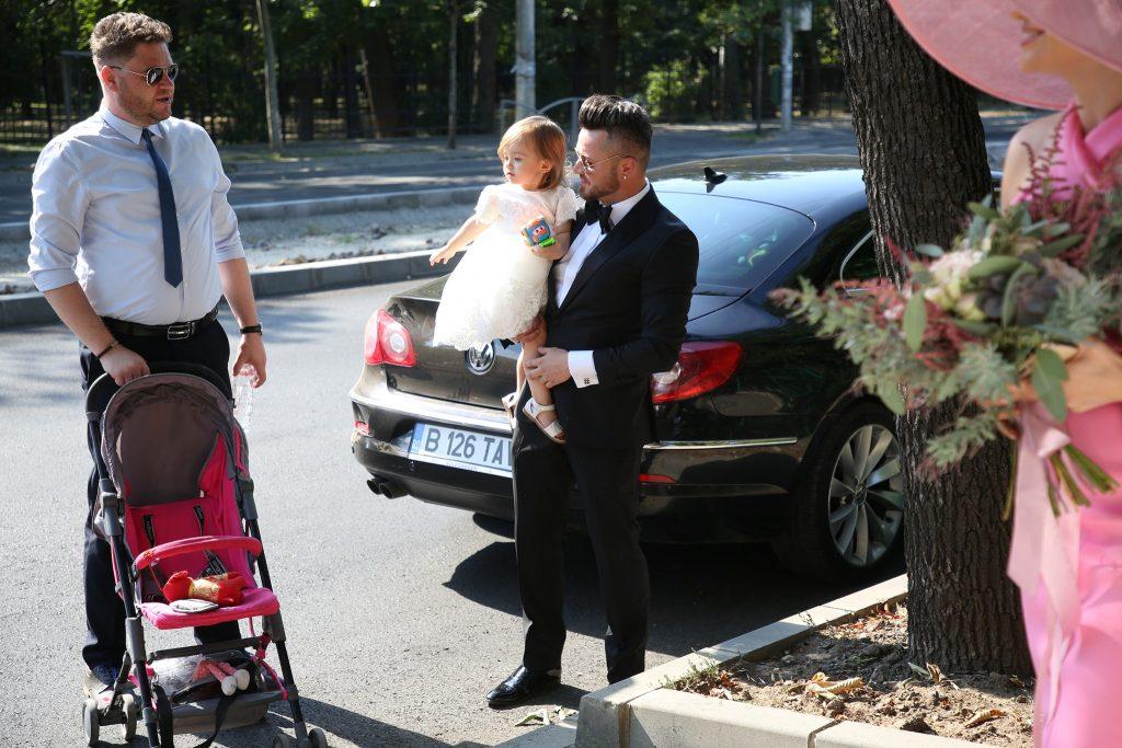 Tavi Clonda o ține în brațe pe fetița sa cea mare, Victoria, iar un prieten de familie îi împinge căruciorul